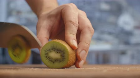 kivi : Cut with a knife on a wooden board closeup kiwi in the kitchen. shred. Stok Video
