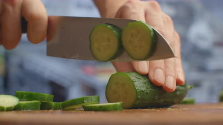 shred : Cut a knife on a wooden board closeup cucumbers in the kitchen. shred.