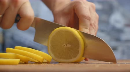 tábua de cortar : Cut with a knife on a wooden board close-up of a lemon in the kitchen. shred.