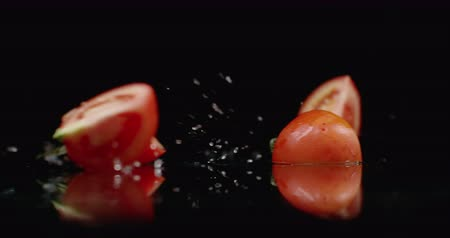 kool : Juicy sliced ​​red tomato fall into 4 parts glass with splashes of water in slow motion on a dark background.