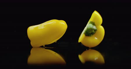 brócolis : Yellow juicy cut bell pepper falling on glass with water splashes in slow motion on a dark background.