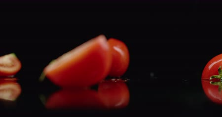 tomates cereja : Juicy sliced ​​red tomato fall into 4 parts glass with splashes of water in slow motion on a dark background.
