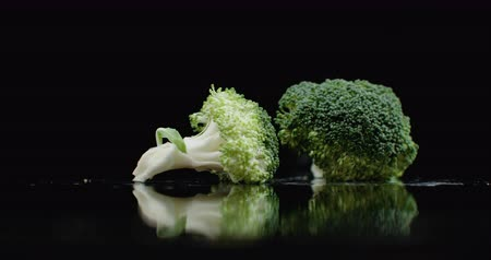 kool : A lot of green fresh broccoli fall on a glass with splashes and drops of water in slow motion on a dark background. Ingredients for Salad, Healthy Food Stockvideo