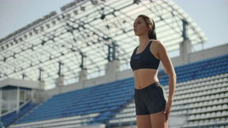 motivados : Beautiful woman athlete at the stadium breathing and preparing to start the race. Motivation and tuning for the race. Concentration and attitude.