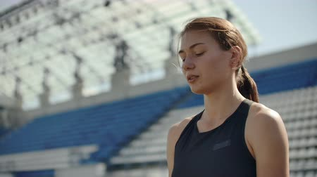 závodní dráha : Slow motion: woman athlete waits for start of race in 400 meters. girl athlete waits for start of race in 100 meters during. Running at the stadium from the pads on the treadmill. Dostupné videozáznamy