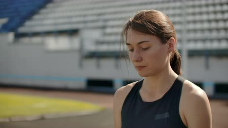 arquibancadas : Slow motion portrait of beautiful woman running on the stadium bleachers with concentrated deep breathing and motivating myself and consciousness for the race. Discard unnecessary emotions