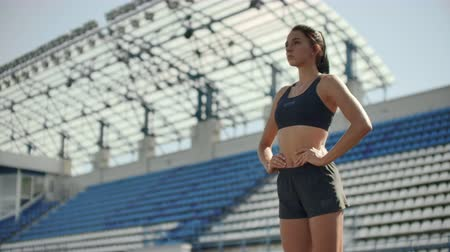 versenypálya : Slow motion: woman athlete waits for start of race in 400 meters. girl athlete waits for start of race in 100 meters during. Running at the stadium from the pads on the treadmill. Stock mozgókép