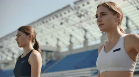 começando : Slow motion: Athlete woman waiting in the starting block on running track.