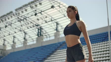 velocista : Slow motion: Athlete woman waiting in the starting block on running track.
