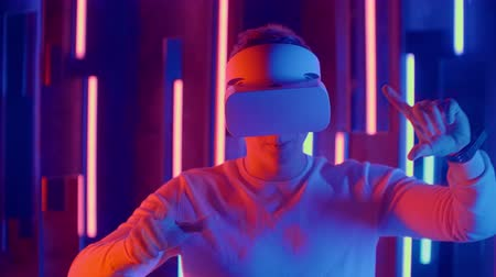 senza volto : Faceless man wearing VR headset in dark space with neon light lamps, user turning head side to side looking virtual reality, shoting through colored flares and bokeh on foreground.