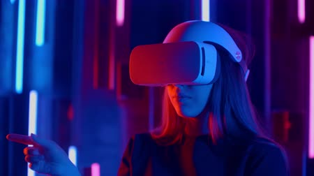 uitvinding : Standing woman trying VR headset in neon lights Stockvideo