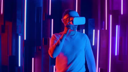 wynalazek : Man wearing VR headset quick slopes from side to side while playing in dark space illuminated neon light. Wideo
