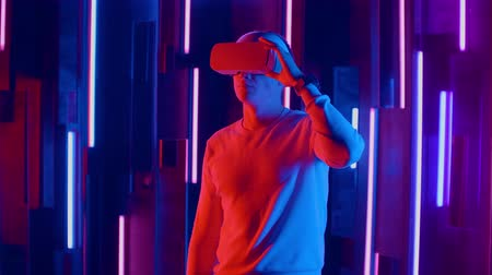 wynalazek : Standing man trying VR headset in neon lights Wideo