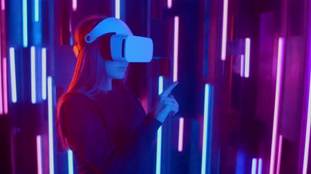 wynalazek : Woman wearing VR headset quick slopes from side to side while playing in dark space illuminated neon light.