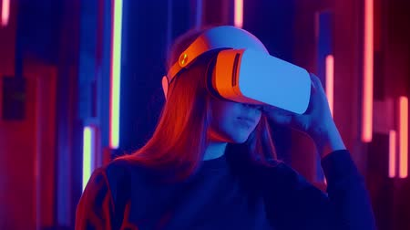 погружение : Woman wearing VR headset quick slopes from side to side while playing in dark space illuminated neon light.