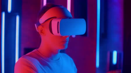 cyberpunk : Man wearing VR headset quick slopes from side to side while playing in dark space illuminated neon light. Stock Footage