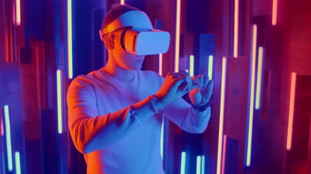 immersione : Young Man putting VR headset on the viewer in neon lights