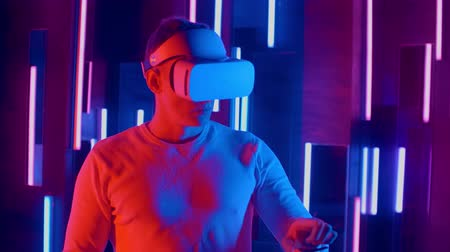 wynalazek : Faceless man wearing VR headset in dark space with neon light lamps, user turning head side to side looking virtual reality, shoting through colored flares and bokeh on foreground.