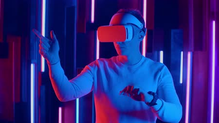 arcades : Young Man in VR headset looks around and wonders how amazing. Virtual reality helmet.
