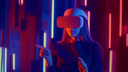 espectador : Young woman putting VR headset on the viewer in neon lights