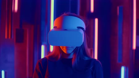 wynalazek : Faceless woman wearing VR headset in dark space with neon light lamps, user turning head side to side looking virtual reality, shoting through colored flares and bokeh on foreground.