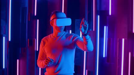 опыт : Young Man putting VR headset on the viewer in neon lights