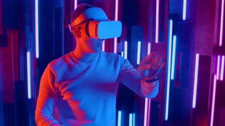 погружение : Man wearing VR headset quick slopes from side to side while playing in dark space illuminated neon light. Стоковые видеозаписи