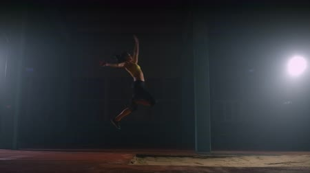 versenypálya : A sporty woman runs up in a stadium and performs a long jump in slow motion in a stadium on a dark background Stock mozgókép