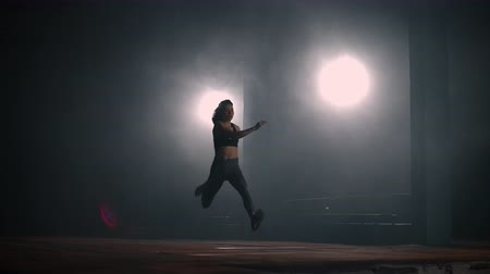 velocímetro : A sporty woman runs up in a stadium and performs a long jump in slow motion in a stadium on a dark background Stock Footage