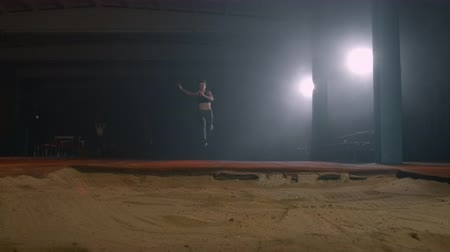 závodní dráha : A sporty woman runs up in a stadium and performs a long jump in slow motion in a stadium on a dark background Dostupné videozáznamy