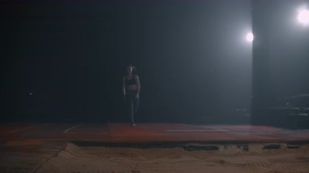 sandpit : Running woman athletics at the stadium on a treadmill performs a triple jump in length and flies into the sand landing on her feet. Slow motion