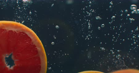 lemoniada : 3 Grapefruit rings Underwater with air bubbles and in slow motion. Fresh and juicy healthy vegetarian.
