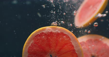 clear liquid : Grapefruit Under water with air bubbles and in slow motion. Fresh and juicy healthy vegetarian. Stock Footage