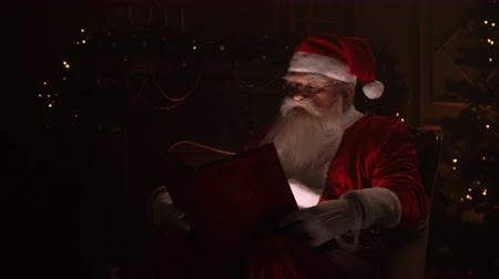 záradék : Santa claus sitting in specially decorated room, reading a magical shining book - holidays and celebrations, christmas spirit concept.