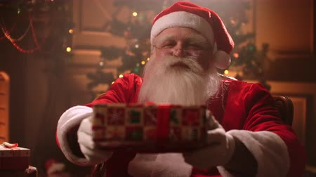 arife : Santa Claus pulls a gift into the camera. Christmas time a real Santa Claus with a beard gives a gift in a box.