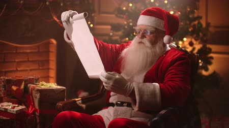 papyrus : Santa Claus holding old scroll of parchment, . Letter, blank. Smiling Santa with scroll paper. Santa list- Santa Claus holding scroll paper Stock Footage