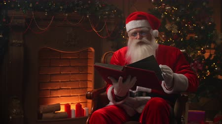 záradék : Joyful authentic santa clause flipping through pages of red covered book, with fireplace and christmas tree on background - christmas spirit concept close up