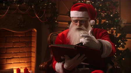 záradék : Realistic santa clause sitting near fireplace and christmas tree, opening a large magical book with shining pages - cristmas spirit, magic, dream concept.