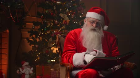 záradék : Joyful santa clause sitting in his rocker in decorated room, reading a book with red cover - holiday mood, christmas spirit concept.