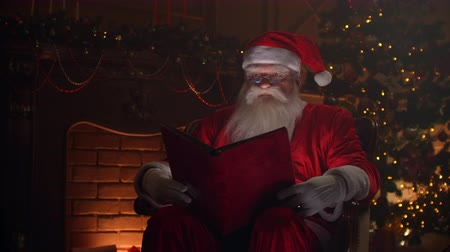 záradék : Senior man in santa clause clothing sitting in atmospheric room, reading a magical shining book with red cover - christmas spirit, holidays and celebrations concept.