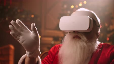 záradék : Santa claus is putting on vr helmet and surfing virtual reality, isolated on christmas spirit, technology concept close up 4k footage. Stock mozgókép
