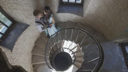 перила : stylish couple posing on spiral staircase