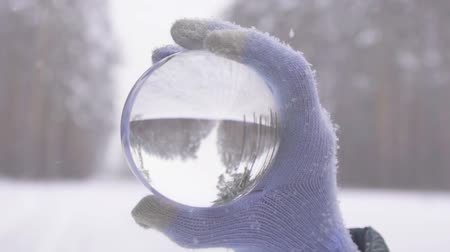 buzlu : glass ball in the hand of a winter forest during a snowfall