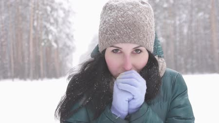 иней : brunette girl in winter forest looking at camera, snow slow mo Стоковые видеозаписи