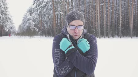 rampouch : freezing man in the cold with glasses in the winter park, rubbing his hands, frost Dostupné videozáznamy
