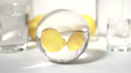 etli : reflection in a glass ball two yellow fresh lemon on white background