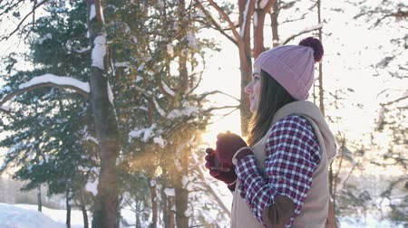 knitted : girl in winter clothes drinking hot mulled wine at sunset in winter forest