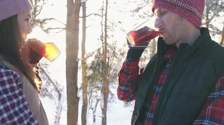 mulled wine : couple of young people in winter clothes drinking hot mulled wine at sunset in winter forest, winter vacation Stock Footage