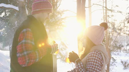 mulled wine : couple of young people in winter clothes drinking hot mulled wine at sunset in winter forest, winter vacation slow mo Stock Footage
