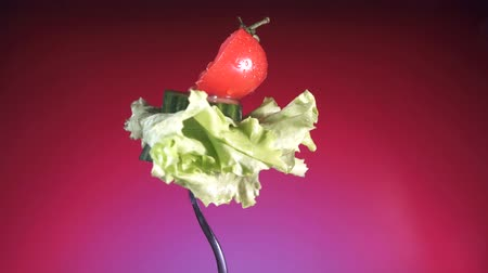 cukorbaj : fork with fresh red sliced tomato and cucumber in water drops and lettuce rotates red background Stock mozgókép